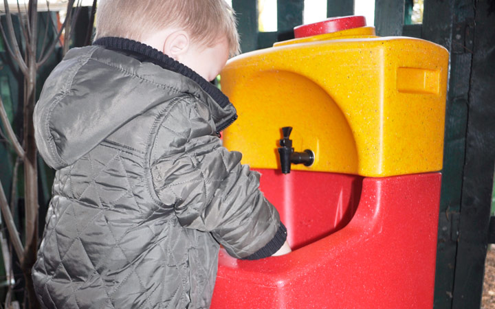 Child washing hands outdoors with a KiddiSynk handwash unit